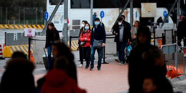 Passengers are seen exiting the port it Civitavecchia early on Jan. 31 after Italy's Ministry of Health confirmed the sick passenger tested negative for the coronavirus.