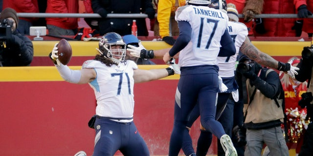 Tennessee Titans' Dennis Kelly (71) celebrating his touchdown catch with quarterback Ryan Tannehill (17) during the first half of the NFL AFC Championship game against the Kansas City Chiefs on Sunday. (AP Photo/Charlie Riedel)