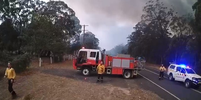Firefighters can be seen preparing to flee the area.