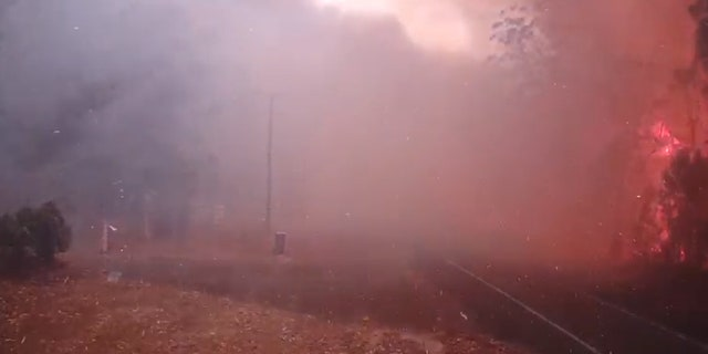 Seconds after firefighters drive away, the main fire line arrives.