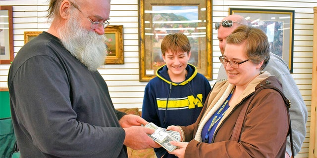 In this Jan. 16, 2020 photo, Howard Kirby, left, gives $43,170 to Kim Fauth-Newberry at a resale store in Owosso Township, Mich.. Kirby's daughter-in-law found the money in a footstool that was donated to the store by Fauth-Newberry. The footstool had belonged to her grandfather, who died last summer. Kirby bought it along with other furniture after Christmas. (Sally York/The Argus-Press via AP)