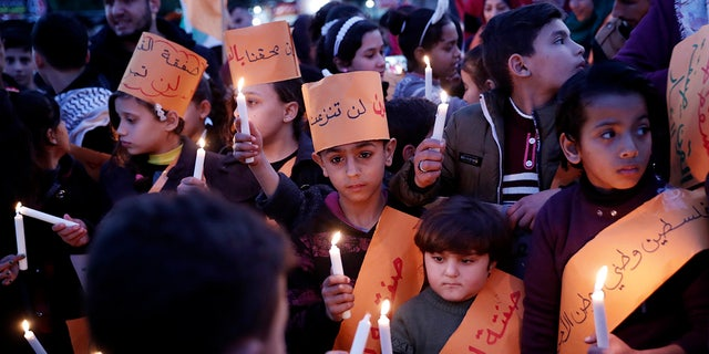 Protesters hold light candles as others wave their national flags during a protest against the Mideast plan announced by the U.S. President Donald Trump, at Jebaliya refugee camp, Gaza Strip, Thursday, Jan. 30, 2020.(AP Photo/Adel Hana)