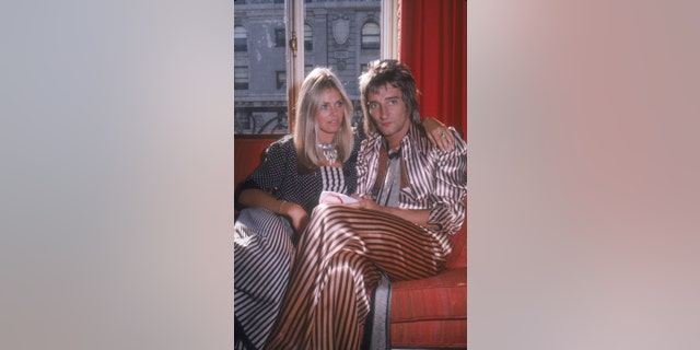 British musician Rod Stewart and his girlfriend, Swedish actress Britt Ekland, sitting on a sofa in a hotel room while on a promotional tour in support of Stewart's album 'Atlantic Crossing,' New York, New York, July 29, 1975.