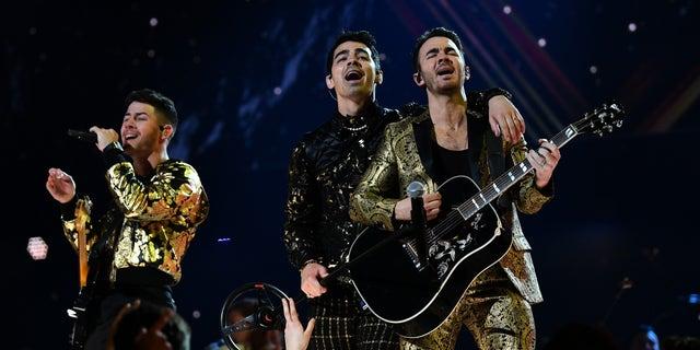 Nick Jonas, Joe Jonas, and Kevin Jonas of music group Jonas Brothers perform onstage during the Grammys.