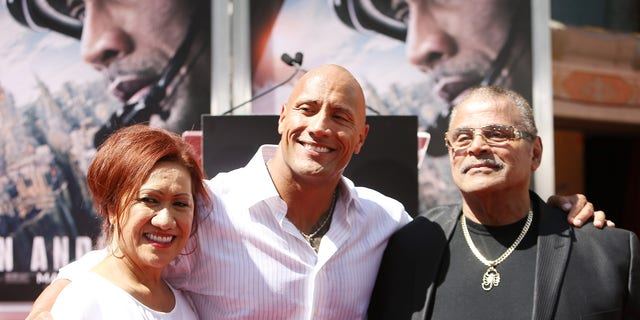 "Dwayne ""The Rock"" Johnson (C) and his mom and dad at the hand/footprint ceremony honoring him in 2015. (Photo by Michael Tran/FilmMagic)"