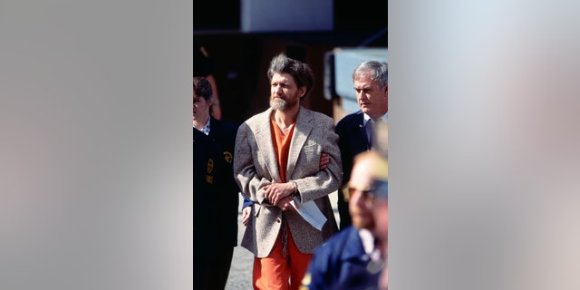 Police officers bring Theodore Kaczynski, aka the Unabomber, to court for arraignment. Kaczynski later pled guilty to the mail bomb attacks that killed three people and injured 23.