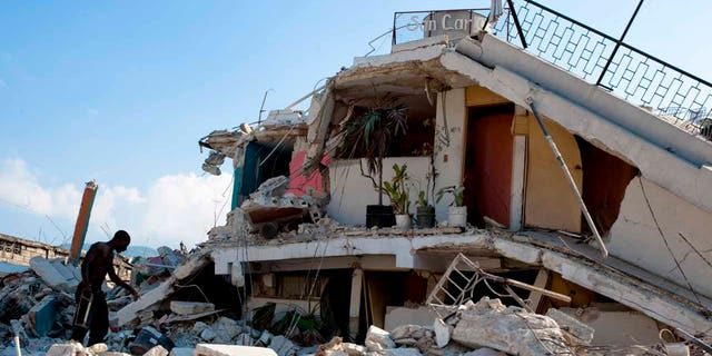 A man searching through the rubble of buildings in the wake of the Jan. 12, 2010 earthquake that devastated Haiti.