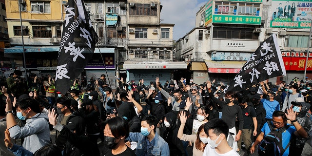 "Protesters march Sunday during a demonstration against ""parallel traders"" who buy goods in Hong Kong to resell in mainland China. (AP Photo/Andy Wong)"