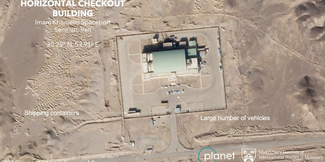 A satellite image taken on Sunday shows a large number of vehicles and shipping contains at a building at Iran's Imam Khomeini Spaceport. (Planet Labs Inc. Middlebury Institute of International Studies via AP)