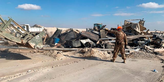U.S. soldiers clear rubble from a site of Iranian bombing at Ain al-Asad air base in Anbar, Iraq, Monday, Jan. 13, 2020. (AP Photo/Ali Abdul Hassan)