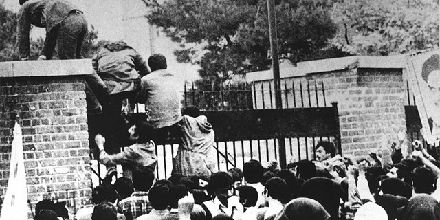 Iranian students climb over the wall of the US embassy in Tehran 04 November 1979.