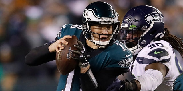 Philadelphia Eagles' Josh McCown (18) tries to get past Seattle Seahawks' Jadeveon Clowney (90) as Miles Sanders (26) tries to defend during the first half of an NFL wild-card playoff football game, Sunday, Jan. 5, 2020, in Philadelphia. (AP Photo/Matt Rourke)