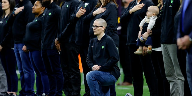 A teacher from the Extra Yard for Teachers charity kneels during the National Anthem prior to the Clemson v LSU game in the College Football Playoff National Championship.