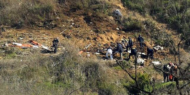 Investigators work the scene of a helicopter crash that killed former NBA basketball player Kobe Bryant, his 13-year-old daughter, Gianna, and several others in Calabasas, Calif. (AP Photo/Mark J. Terrill)
