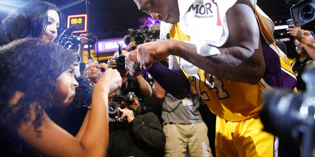 FILE - In this April 13, 2016 file photo Los Angeles Lakers' Kobe Bryant, right, fist-bumps his daughter Gianna after the last NBA basketball game of his career. (AP Photo/Jae C. Hong, file)