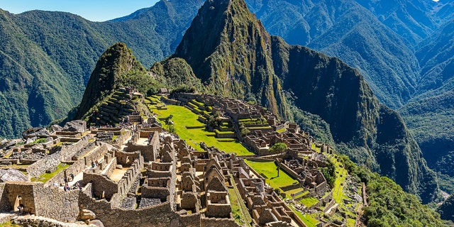 Machu Picchu during daytime with tourists visiting the site near the city of Cusco, Peru. (iStock).