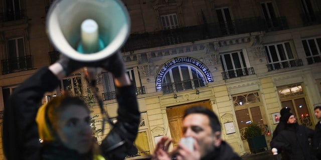 A protestor speaks in a megaphone during a demonstration in front of the Bouffes du Nord theatre in Paris on January 17, 2020 as the French president attends a play. - Protestors demonstrate against French president's policies on pension reform. (Photo by Lucas BARIOULET / AFP) (Photo by LUCAS BARIOULET/AFP via Getty Images)