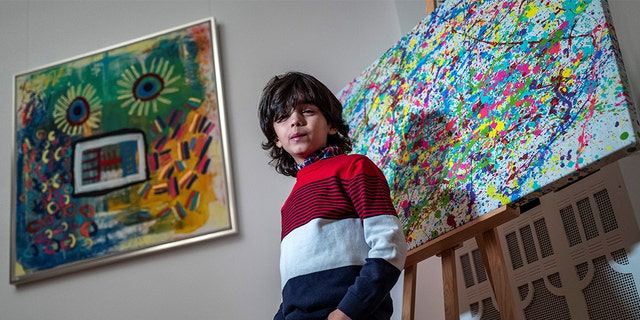 """7-year-old German artist Mikail Akar poses in front of a print edition of his """"Champi"""" painting (right) and his painting """"Sonnenblume Mensch"""" (Sunflower Man) (left) prior to the opening of his """"Manus 11"""" exhibition in Berlin on December 13, 2019. (Photo by JOHN MACDOUGALL/AFP via Getty Images)"""
