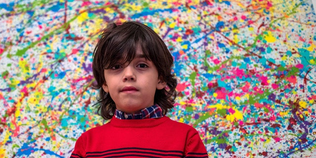 """7-year-old German artist Mikail Akar poses in front of a limited print edition of his """"Champi"""" painting, prior to the opening of his """"Manus 11"""" exhibition in Berlin on December 13, 2019."""