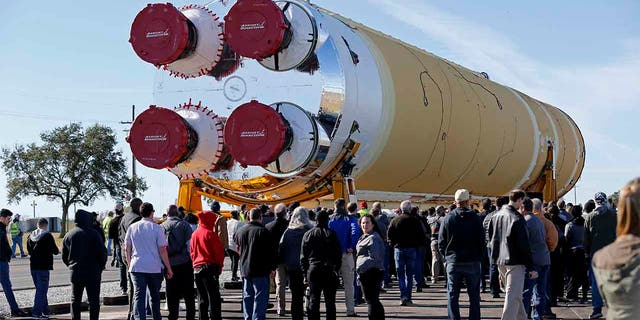 Employees and contractors watch as the core stage of NASA's Space Launch System rocket, that will be used for the Artemis 1 Mission, is moved to the Pegasus barge, at the NASA Michoud Assembly Facility where it was built, in New Orleans. (AP Photo/Gerald Herbert)