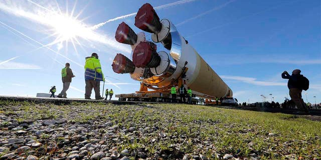 Security and safety personnel walk with the core stage of NASA's Space Launch System rocket, that will be used for the Artemis 1 Mission, as it is moved to the Pegasus barge, at the NASA Michoud Assembly Facility where it was built, in New Orleans. (AP Photo/Gerald Herbert)