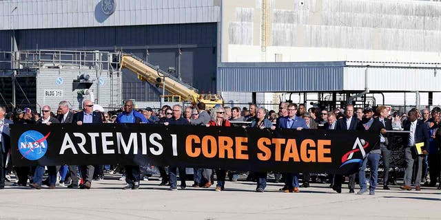 Workers and contractors who worked on the core stage of NASA's Space Launch System rocket, that will be used for the Artemis 1 Mission, follow the rocket as it is transported to the Pegasus barge at the NASA Michoud Assembly Facility where it was built, in New Orleans. (AP Photo/Gerald Herbert)