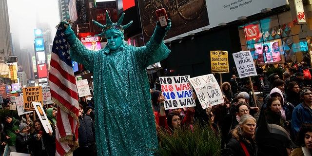 People marched as they take part in an anti-war protest at Times Square. (REUTERS/Eduardo Munoz)