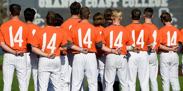 The Orange Coast College baseball players stands for the national anthem while wearing shirts with the number 14 on their backs for late head coach John Altobelli, who died in a helicopter crash alongside former NBA basketball player Kobe Bryant in Costa Mesa, Calif., Tuesday, Jan. 28, 2020. (AP Photo/Kelvin Kuo)