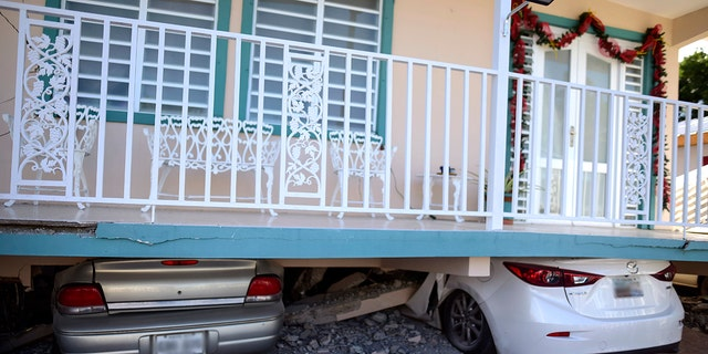 Cars were crushed under a home in Guanica that collapsed after Monday's earthquake. (AP Photo/Carlos Giusti)