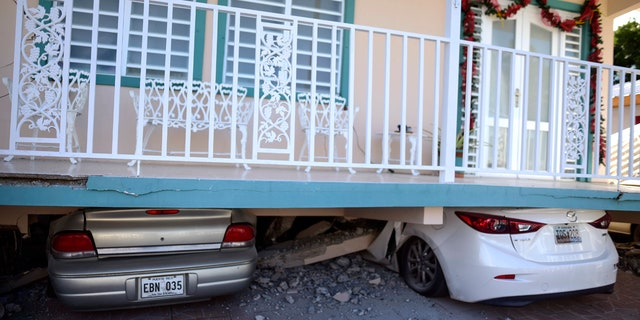 Cars are crushed under a home that collapsed after an earthquake hit Guanica, Puerto Rico, Monday, Jan. 6, 2020.