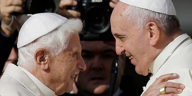Pope Francis, right, hugging Pope Benedict XVI prior to the start of a meeting with elderly faithful in St. Peter's Square at the Vatican in 2014. (AP Photo/Gregorio Borgia, File)