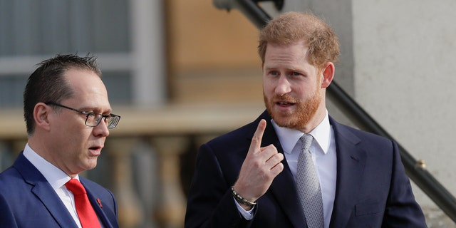 Prince Harry gestures in the gardens at Buckingham Palace in London, Thursday, Jan. 16 ahead of hosting the Rugby League World Cup 2021 draw.