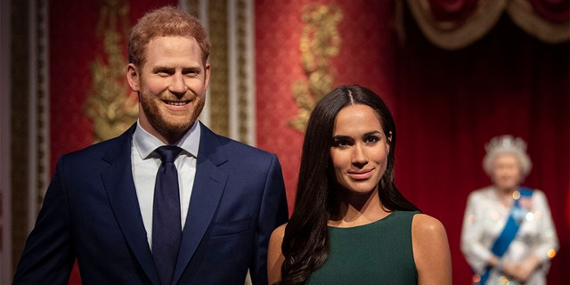 The figures of Britain's Prince Harry and Meghan, Duchess of Sussex, left, are moved from their original positions next to Queen Elizabeth II, Prince Philip and Prince William and Kate, Duchess of Cambridge, at Madame Tussauds in London following their bombshell announcement.