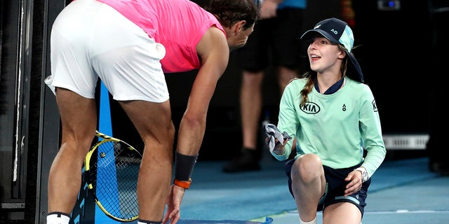 Spain's Rafael Nadal hands a ball girl his bandana after a ball hit her during his second-round match against Federico Delbonis of Argentina at the Australian Open tennis championship in Melbourne, Thursday, Jan. 23, 2020. (AP Photo/Dita Alangkara)