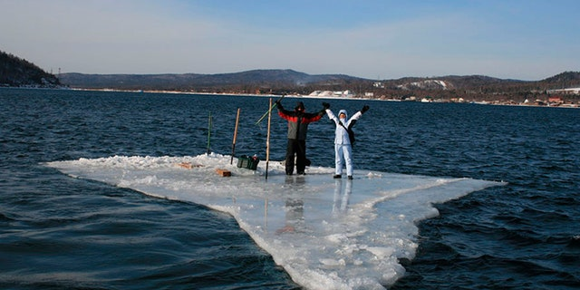 In this Tuesday, Jan. 28, 2020 photo released by the Russia Emergency Situations Ministry press service, showing two fishermen using a smaller piece of ice as a raft and try to row to the land.