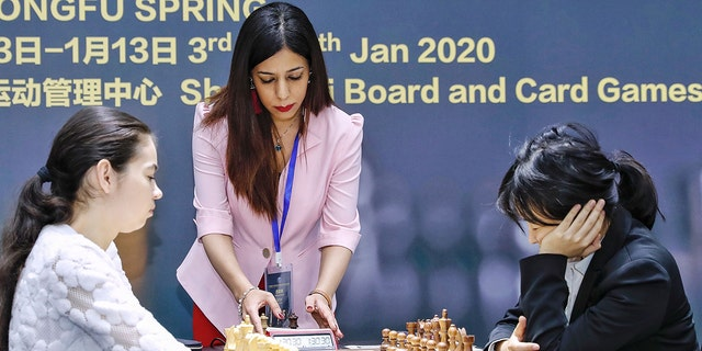 Shohreh Bayat (C), chief arbiter for the match between Aleksandra Goryachkina (front L) of Russia and Ju Wenjun (front R) of China, prepares for the match during the 2020 International Chess Federation (FIDE) Women's World Chess Championship in Shanghai on January 11, 2020. (Photo by STR/AFP via Getty Images)