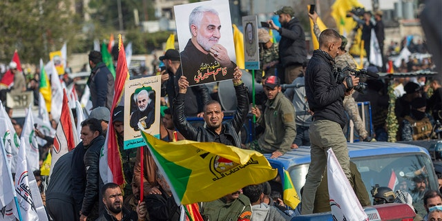 """Mourners march during the funeral of Iran's top general Qassem Soleimani, 62, Abu Mahdi al-Muhandis, deputy commander of Iran-backed militias in Iraq known as the Popular Mobilization Forces and fellow militant leaders, in Baghdad, Iraq, Saturday, Jan. 4, 2020. Thousands of mourners chanting """"America is the Great Satan"""" marched in a funeral procession Saturday through Baghdad for Iran's top general and Iraqi militant leaders, who were killed in a U.S. airstrike. (AP Photo/Nasser Nasser)"""