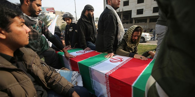 "Iraqis surround a coffin, draped in an Iranian national flag, during the funeral procession of Iraqi paramilitary chief Abu Mahdi al-Muhandis, Iranian military commander Qasem Soleimani, and eight others, in the capital Baghdad's district of al-Jadriya, near the high-security Green Zone, on January 4, 2020. - Thousands of Iraqis chanting ""Death to America"" joined the funeral procession for Iranian military commander Qasem Soleimani and Muhandis, both killed in a US air strike. The cortege set off around Kadhimiya, a Shiite pilgrimage district of Baghdad, before heading to the Green Zone government and diplomatic district where a state funeral was to be held attended by top dignitaries. In all, 10 people -- five Iraqis and five Iranians -- were killed in Friday morning's US strike on their motorcade just outside Baghdad airport. (Photo by AHMAD AL-RUBAYE / AFP) (Photo by AHMAD AL-RUBAYE/AFP via Getty Images)"