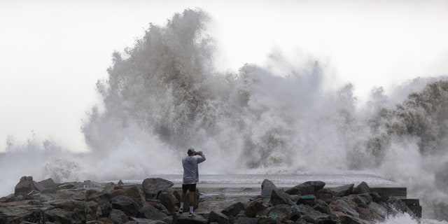 A man takes a snapshot of the waves hitting the breakwater in Barcelona, Spain, Wednesday, Jan. 22, 2020.