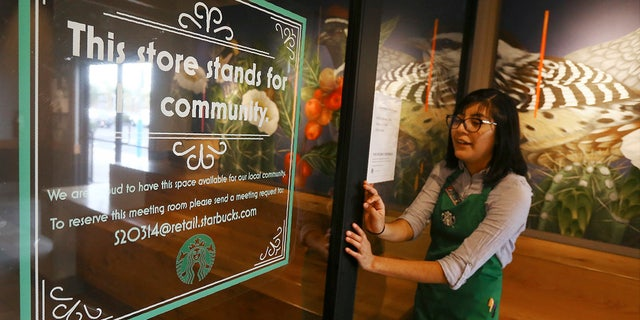In this Wednesday, Jan. 15, 2020, photo, Belith Ariza, a barista trainer at Starbucks, opens the doors to the community meeting space at a local Starbucks Community Store, in Phoenix.  (AP Photo/Ross D. Franklin)