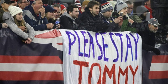 New England Patriots fans stand by a sign supporting quarterback Tom Brady in the first half of an NFL wild-card playoff football game between the Patriots and the Tennessee Titans, Saturday, Jan. 4, 2020, in Foxborough, Mass. Brady's contract expires at the end of the season. (AP Photo/Elise Amendola)