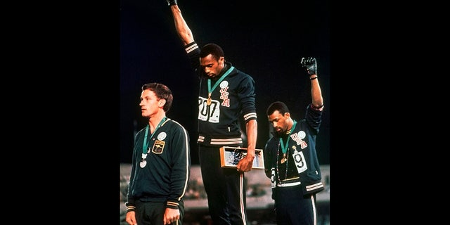 U.S. athletes Tommie Smith, center, and John Carlos, right, raise their gloved fists after Smith received the gold and Carlos the bronze for the 200 meter run at the Summer Olympic Games in Mexico City, Oct. 16, 1968. (Associated Press)