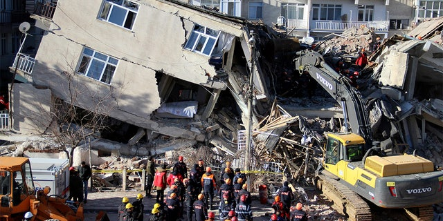 Rescuers work on a collapsed building after a strong earthquake struck in Elazig in the eastern Turkey, Saturday, Jan. 25, 2020. The earthquake rocked eastern Turkey on Friday, causing some buildings to collapse and killing scores of people, Turkish officials said. (IHA via AP)