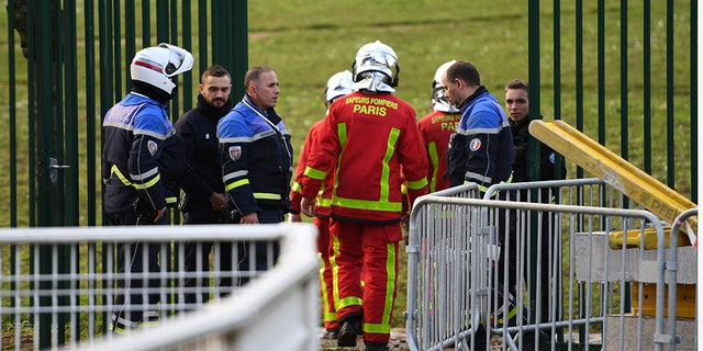 Police and firefighters gather in a park south of Paris on Friday where a man was shot and killed by officers after stabbing passers-by.