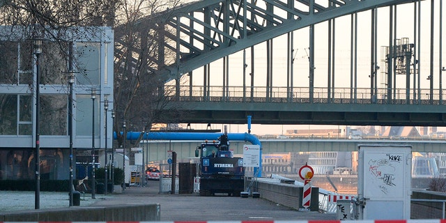The excavator that uncovered the bomb stands in front of the Hohenzollern Bridge in Cologne on Tuesday. (Roberto Pfeil/dpa via AP)