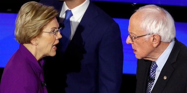 Democratic presidential candidate Sen. Elizabeth Warren, D-Mass., left and Sen. Bernie Sanders, I-Vt., talk Tuesday, Jan. 14, 2020, after a Democratic presidential primary debate hosted by CNN. (AP Photo/Patrick Semansky)