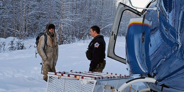 Tyson Steele, left, speaks with Helo 3 Tactical Flight Officer Zac Johnson after being stranded in the wilderness for 23 days.