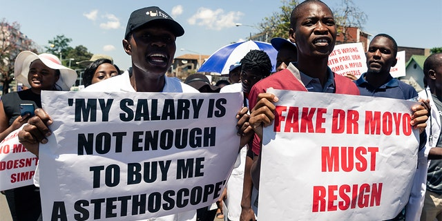 Doctors hold banners during a protest march by senior medical doctors in Harare in December 2019. The doctors petitioned Zimbabwe's parliament, demanding improved working conditions and the reinstatement of 448 junior doctors fired for taking part in a two-month long strike over low salaries. (Photo by Jekesai NJIKIZANA / AFP) (Photo by JEKESAI NJIKIZANA/AFP via Getty Images)