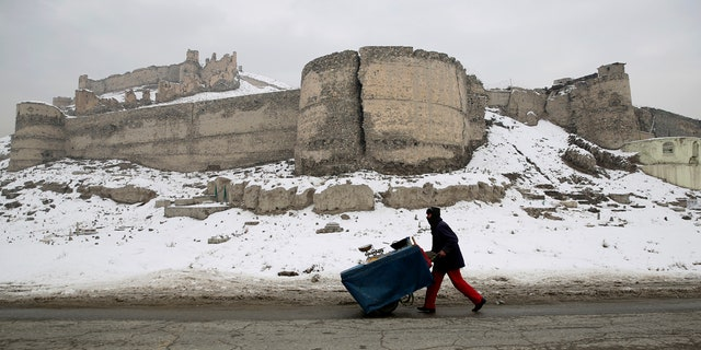 An Afghan street vendor pulls his hand cart after a heavy snowfall in Kabul, Afghanistan, Tuesday, Jan. 14, 2020.