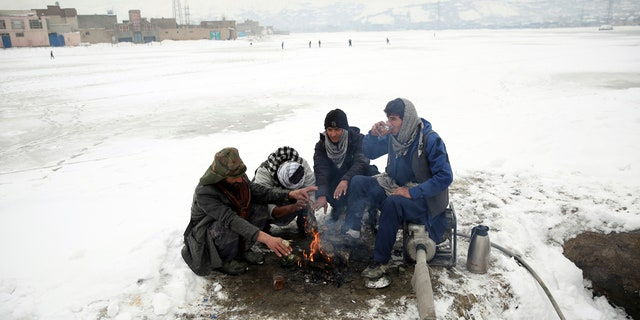 People sit around a fire to warm themselves after a heavy snowfall in Kabul, Afghanistan, Tuesday, Jan. 14, 2020.